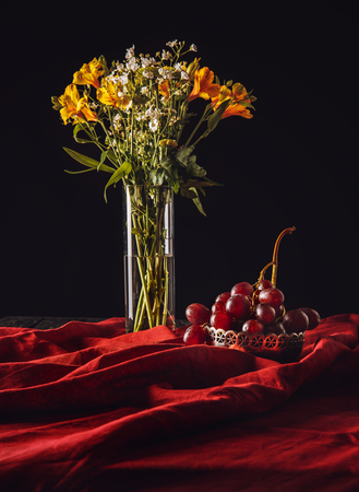still life of grapes in metal bowl with flowers in vase on red drapery Stock Photo - 105956737