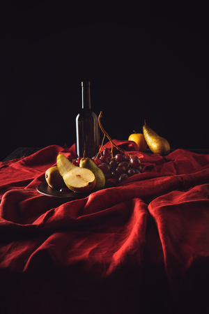 still life with different fruits and wine bottle on red drapery on black Stock Photo