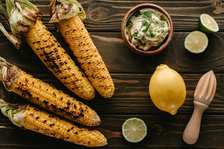 top view of grilled corn, lime slices, lemon, wooden squeezer and cream with parsley on wooden table Stockfoto