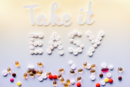 top view of lettering take it easy made by white pills near various tablets on colorful background