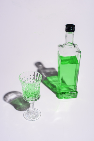 crystal glass and bottle of absinthe on white Stock Photo