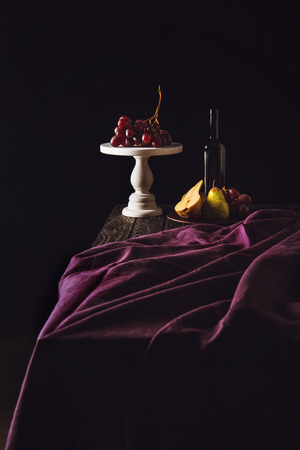 still life with fruits and bottle of wine on burgundy drapery on black Stock Photo