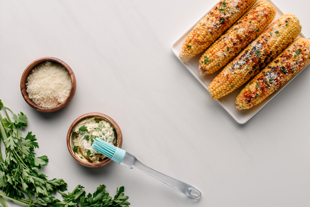 top view of plate with grilled corn, spice, cooking brush and butter with parsley on marble table