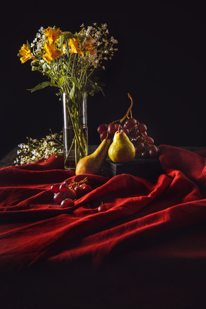 still life with ripe fruits and flowers in vase on red drapery on black