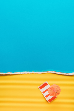 top view of little cocktail umbrella and bedding on yellow and blue paper backdrop