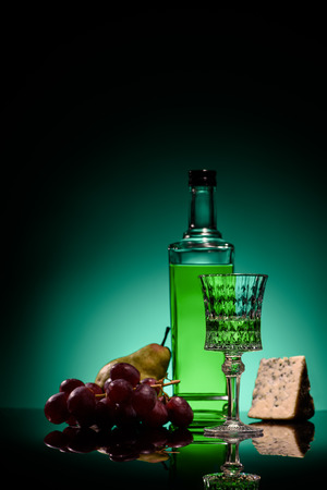 close-up shot of absinthe with pear, grapes and cheese on mirror surface on dark blue background