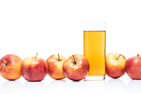 close up view of glass of apple juice and fresh apples isolated on white