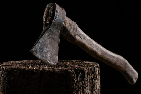 close up view of vintage axe on wooden stump isolated on black 写真素材