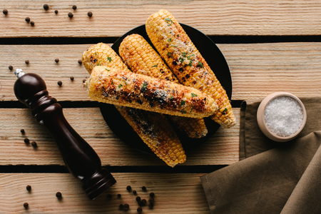 top view of grilled corn, pepper grinder and salt on wooden table