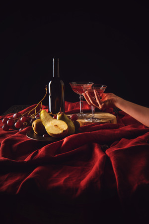 cropped shot of woman taking crystal glass of wine from table on black Stock Photo - 105957266