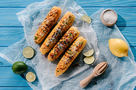 top view of grilled corn on baking paper with lime slices, lemon, salt and wooden squeezer on table Stockfoto