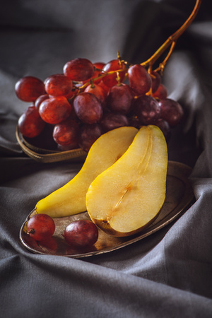 close-up shot of sliced pear and red grapes on grey drapery