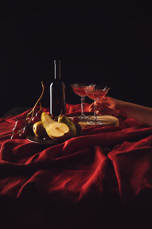 still life with fruits and wine on red drapery on black Stock Photo - 105957305
