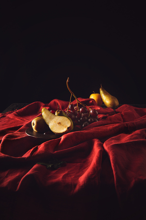 close-up shot of grapes and pears on red drapery
