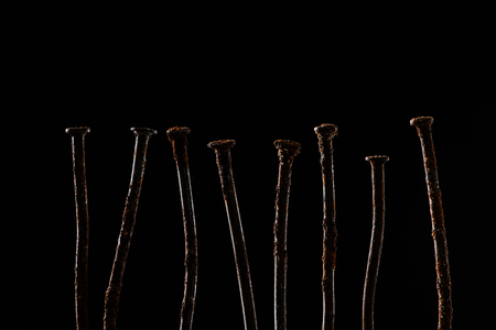 close up view of vintage rusty nails isolated on black