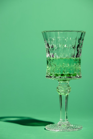 close-up shot of crystal glass of absinthe isolated on green