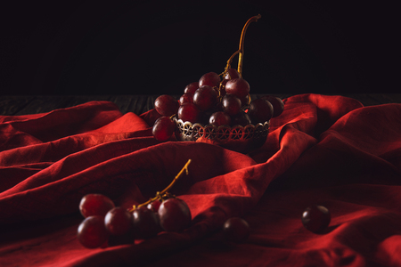 close-up shot of grapes in vintage metal bowl on red drapery on black Banco de Imagens