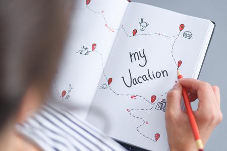 vue partielle, de, femme, à, crayon, tenue, cahier, à, mes vacances, inscription, voyage, concept Banque d'images
