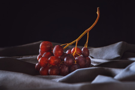 close-up shot of ripe red grapes on grey drapery on black