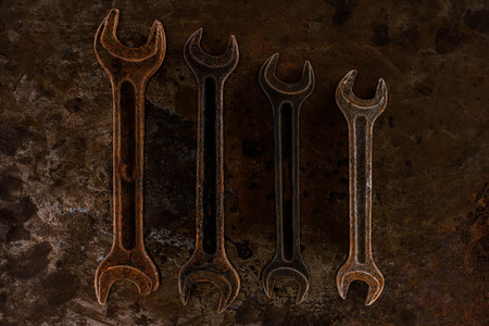 top view of arrangement of vintage wrenches on rusty surface