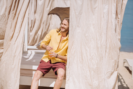 handsome smiling young man holding glass of cocktail while sitting in bungalow at beach