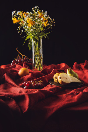 still life with different fruits and flowers in vase on red drapery on black