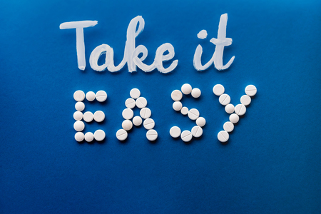 top view of lettering take it easy made by white pills on blue background Imagens