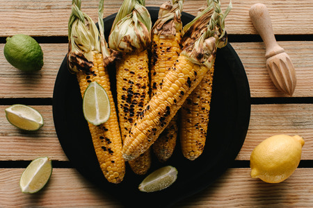 top view of grilled corn on plate surrounded by lime slices and lemon with squeezer on wooden table