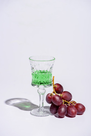 crystal glass of absinthe with branch of grapes on white Stock Photo