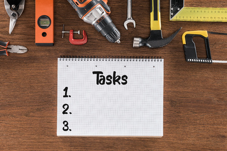 top view of textbook with lettering tasks near various tools on wooden table Stock Photo