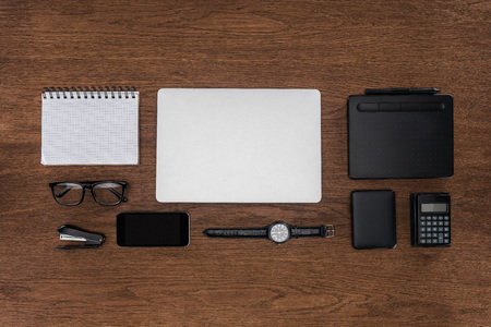 top view of workplace with arranged empty textbook, laptop, wristwatch and smartphone on wooden table
