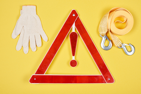 top view of warning triangle road sign, gloves and car tow rope isolated on yellow Banco de Imagens - 105987379