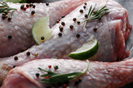 close up view of raw chicken legs with pepper corns, rosemary and lime