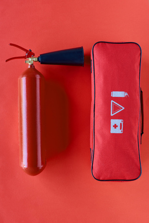 top view of fire extinguisher and automotive handbag on red background