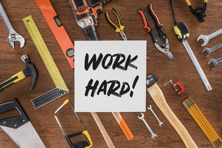 top view of paper with lettering work hard near arranged various tools on wooden table Stock Photo