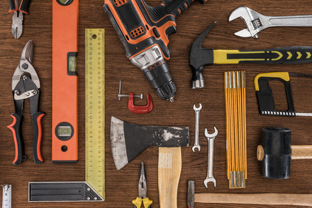 top view of axe, electric drill, spirit level, hammers and various tools on wooden table