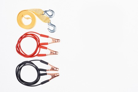 top view of arranged car tow rope and jump start cables isolated on white
