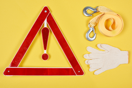 top view of warning triangle road sign, gloves and car tow rope isolated on yellow Stock fotó