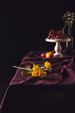 beautiful flowers lying on table with fruits on background Stock Photo - 105986967