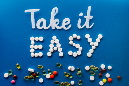 top view of lettering take it easy made by white pills near various tablets on blue background Imagens - 105986971