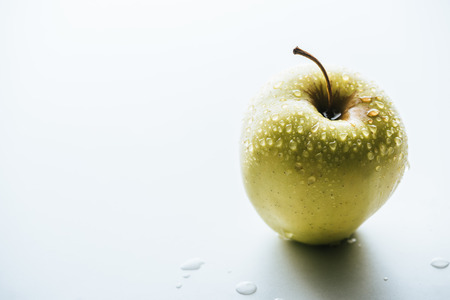 close up view of fresh green apples with water drops on white background