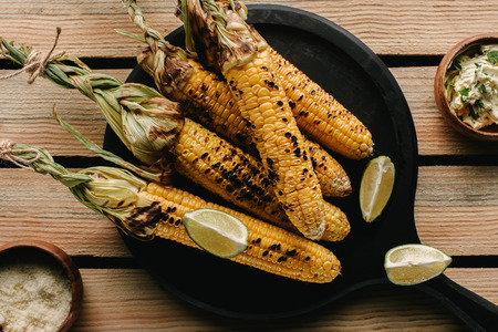 top view of grilled corn, lime slices and butter with parsley on wooden table Stok Fotoğraf
