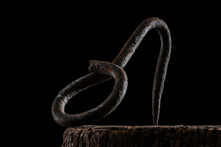 close up view of vintage hook on wooden stump isolated on black