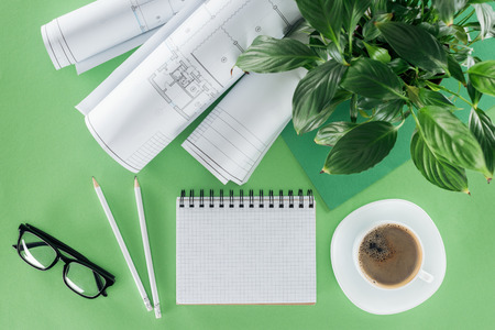 top view of architect workplace with empty textbook, blueprints, coffee and plant on table