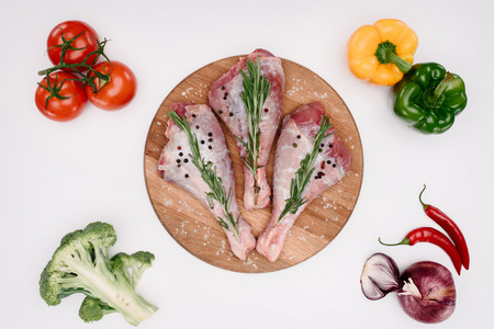 top view of uncooked chicken legs with rosemary on cutting board with raw vegetables near, isolated on white Stock Photo