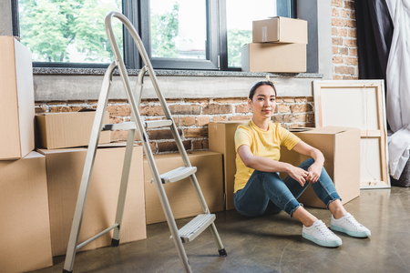 young asian woman surrounded sitting on floor after relocation