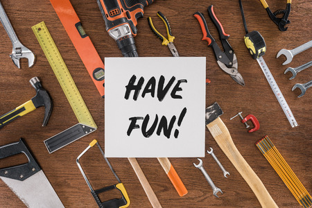 top view of paper with lettering have fun near arranged various tools on wooden table Stock Photo