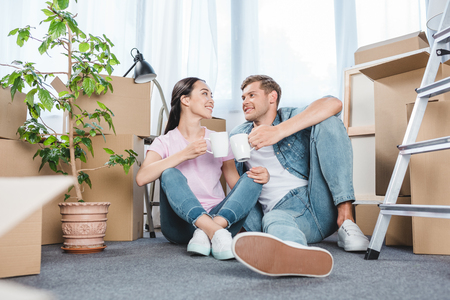 smiling young couple sitting on floor together and clinking mugs with coffee while moving into new home 免版税图像