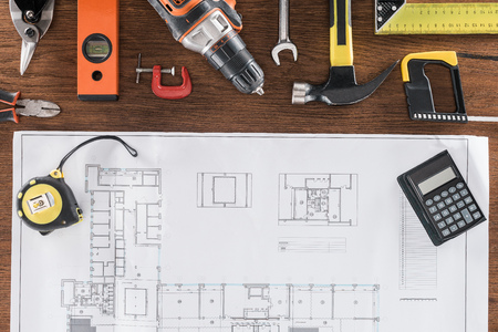 top view of architect blueprint, tape measurement, calculator and various tools on wooden table Stock Photo