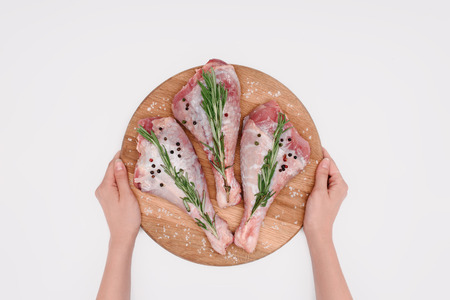cropped view of woman holding wooden cutting board with turkey legs and rosemary, isolated on white